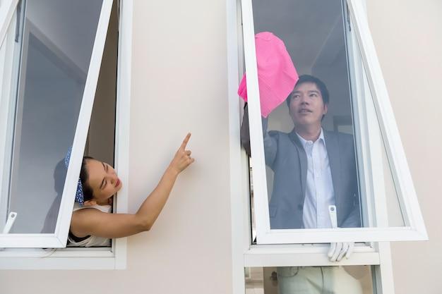 Femme ordre mari à nettoyer la fenêtre de la maison Photo Premium