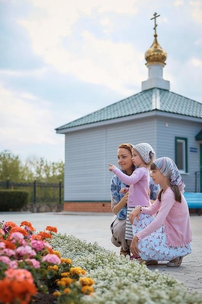 Femme orthodoxe russe dans un foulard avec ses filles près de l'église Photo Premium
