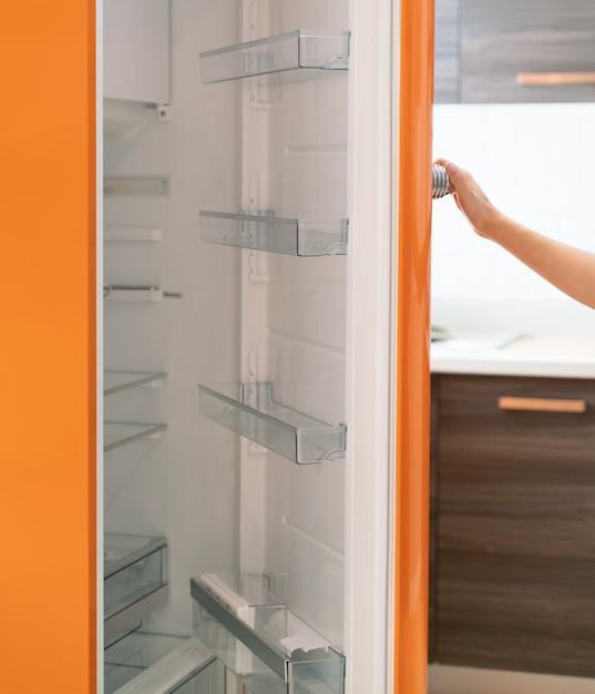 Femme Ouvrir La Porte Du Réfrigérateur Dans La Cuisine Photo Premium