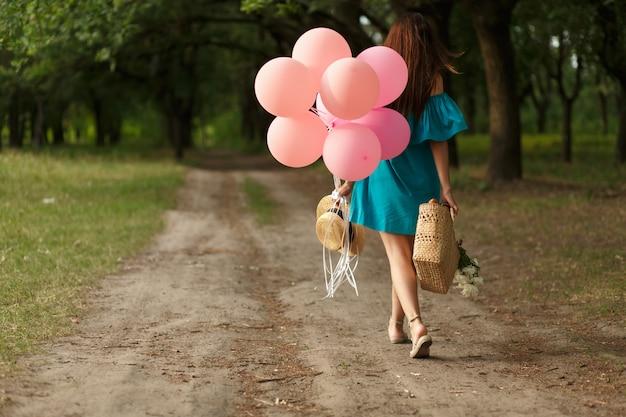 Femme avec un panier en osier, un chapeau, des ballons roses et des fleurs marchant sur une route de campagne Photo Premium