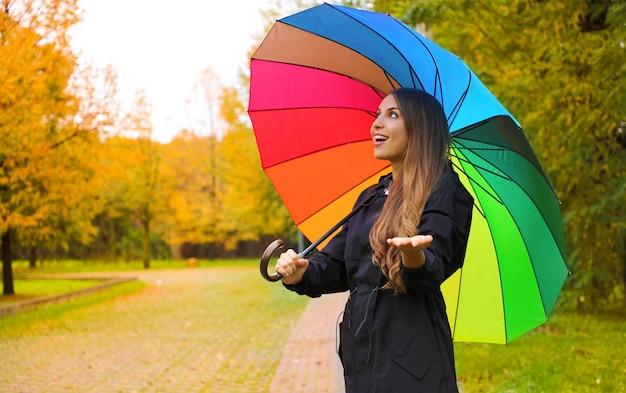 Femme Avec Parapluie Coloré Vérifiant La Pluie Dans Le Parc De La Ville Photo Premium