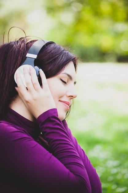 Femme en parc d'écoute de musique avec des écouteurs. Photo Premium