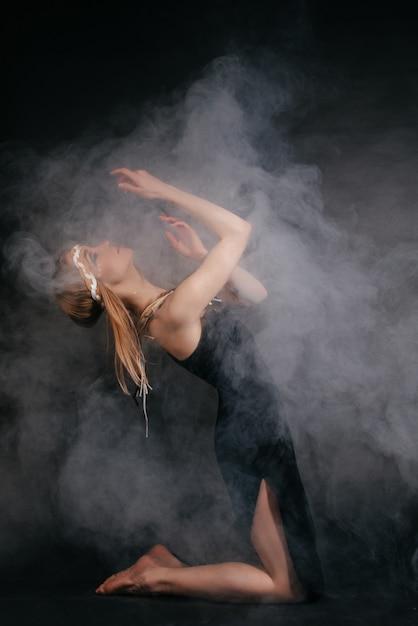 Femme parfaite en costume d'indiens d'amérique en fumée sur fond gris Photo Premium