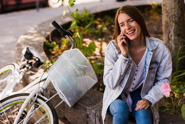 Femme parlant au téléphone à côté du vélo Photo gratuit