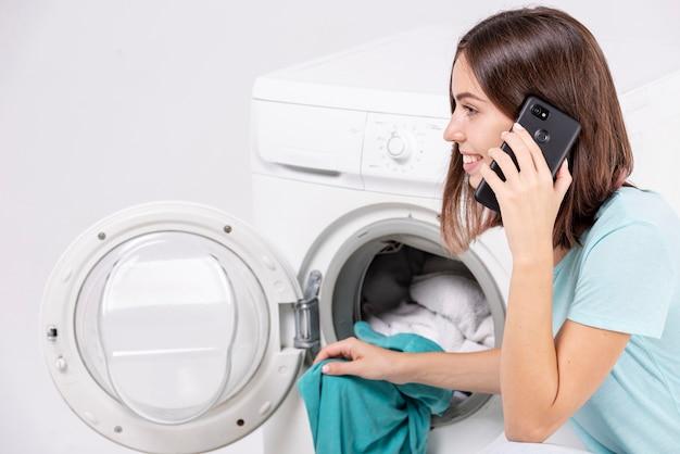 Femme parlant au téléphone en faisant la lessive Photo gratuit