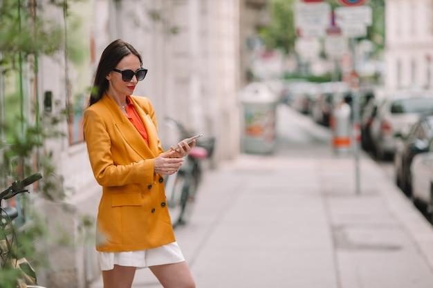 Femme parle par son smartphone en ville. jeune touriste attrayant en plein air dans la ville italienne Photo Premium