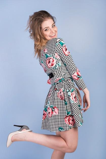 Femme passionnée souriante en robe et talons hauts Photo gratuit