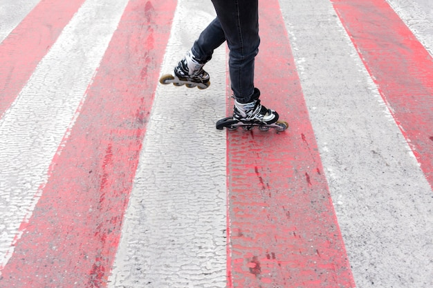 Femme en patins à roues alignées sur le passage pour piétons Photo gratuit