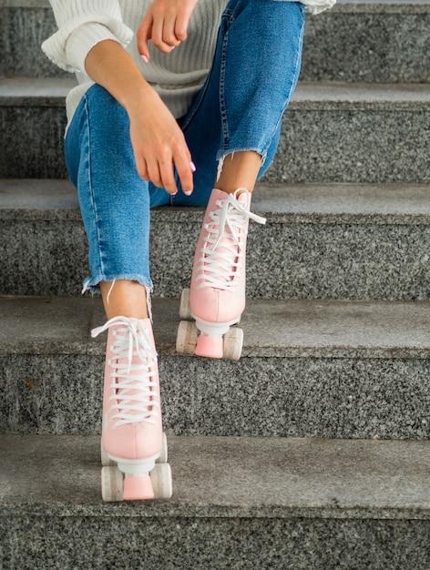 Femme avec des patins à roulettes posant dans les escaliers Photo gratuit