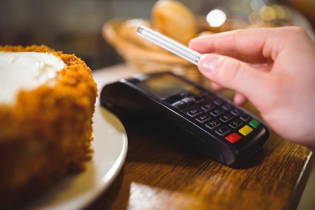Femme payer projet de loi par smartphone à l'aide de la technologie nfc Photo gratuit