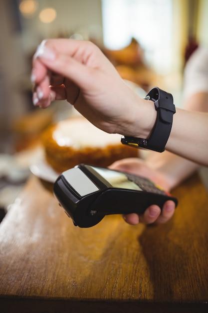 Femme payer projet de loi par smartwatch en utilisant la technologie nfc Photo gratuit