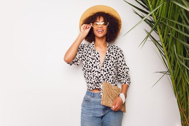 Femme à La Peau Foncée En Jeans Et Chapeau De Paille Qui Pose En Studio Sur Fond Blanc Avec Sac Dans Le Style De Bali. Humeur Calme. Photo gratuit
