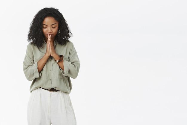 Femme à La Peau Foncée Pliant La Tête En Bas Fermant Les Yeux Debout Paisible Et Détendu Avec Les Mains En Prière Photo gratuit