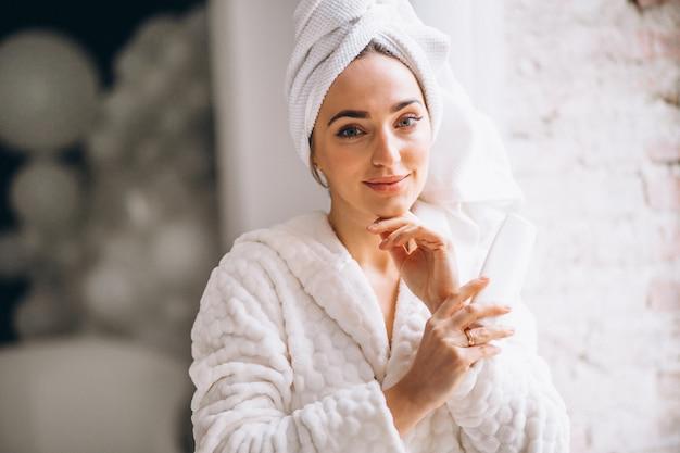 Femme en peignoir avec une lotion pour le corps Photo gratuit