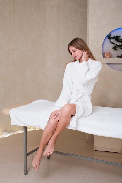 Femme en peignoir posant sur une table de massage au spa Photo gratuit