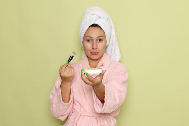 Femme En Peignoir Rose Faisant Du Maquillage Photo gratuit