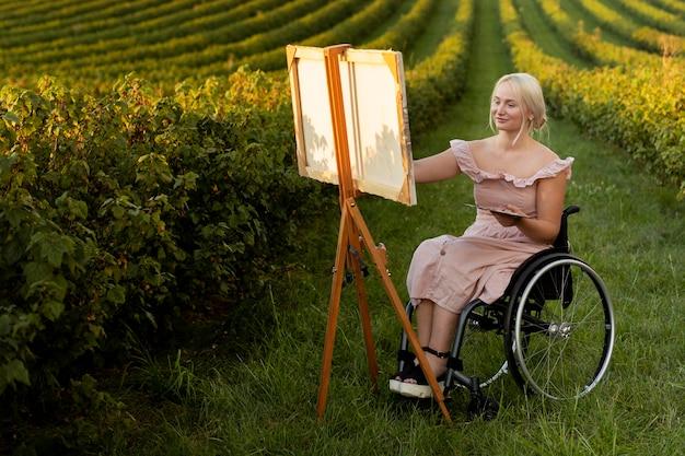Femme En Peinture En Fauteuil Roulant à L'extérieur Photo gratuit