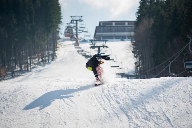 Femme pensionnaire sur le snowboard après avoir sauté par-dessus la pente Photo Premium