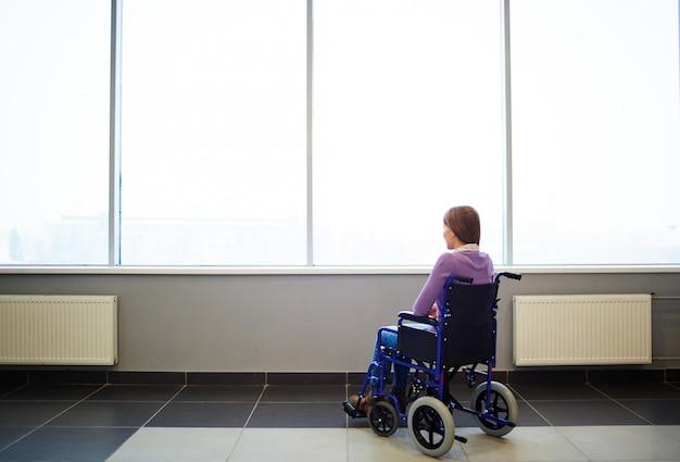 Femme pensive en fauteuil roulant Photo gratuit