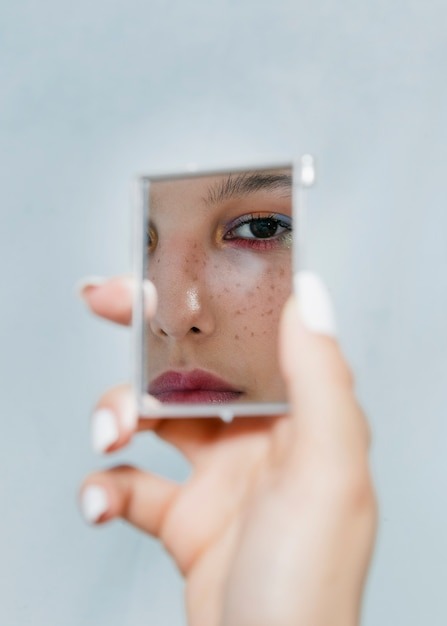 Femme pensive regardant dans un miroir Photo gratuit