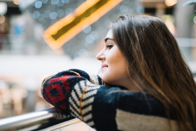 Femme pensive se penchant sur la rambarde Photo gratuit