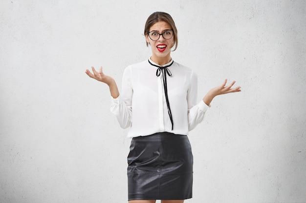 Une Femme Perplexe Porte Des Lunettes élégantes, Un Chemisier Et Une Jupe, Des Gestes Perplexes, A Déplu Au Regard Photo gratuit