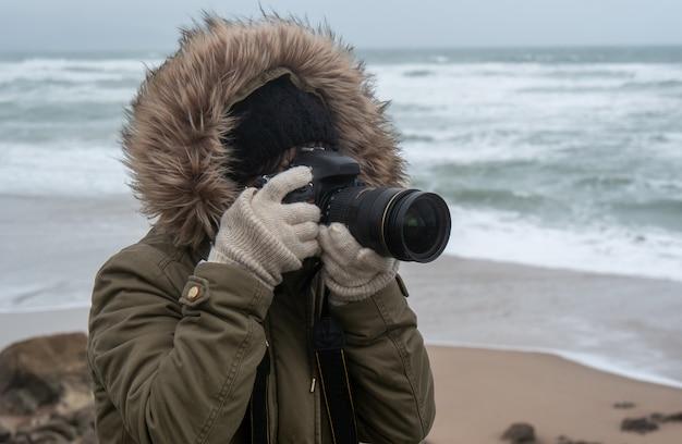 Femme photographe prenant une photo au bord de la mer en hiver Photo Premium