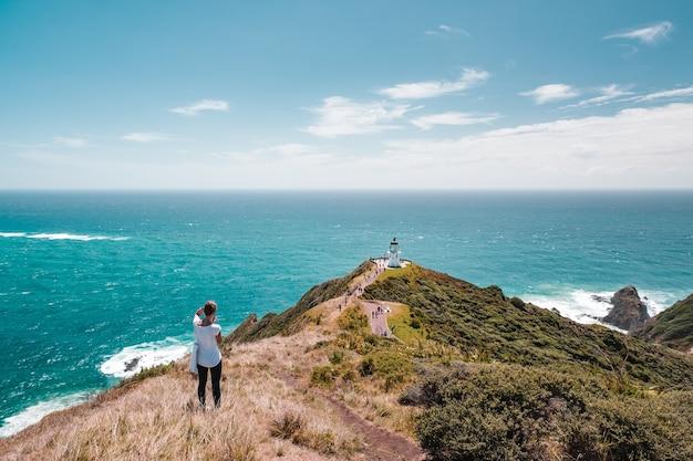 Une Femme Photographe Prend Une Photo Beau Paysage De Paysage Du Ciel Bleu De La Montagne Verte Et Du Phare, Le Bâtiment Patrimonial. Cape Reinga, île Du Nord, Nouvelle-zélande. Photo Premium