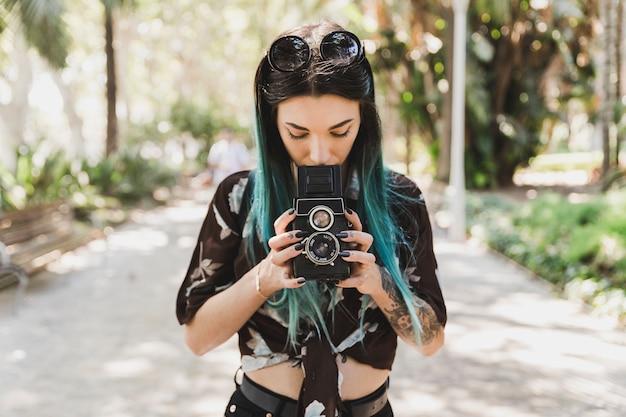 Femme photographiant avec une vieille lentille jumelle reflex Photo gratuit