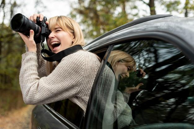 Femme photographiant d'une voiture en mouvement Photo gratuit