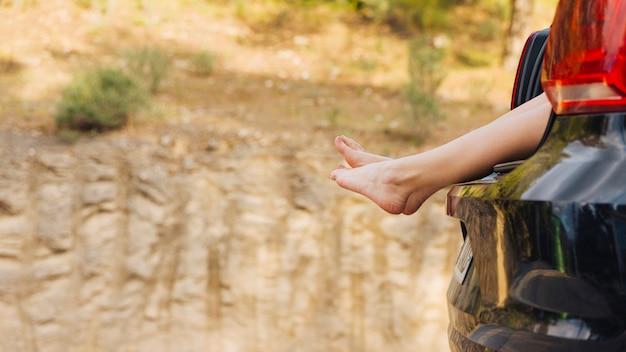 Femme, pieds, hors, compartiment machine Photo gratuit