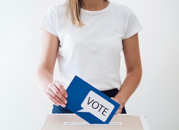 Femme Plaçant Une Carte Bleue Avec Un Message De Vote Dans Une Boîte Photo Premium