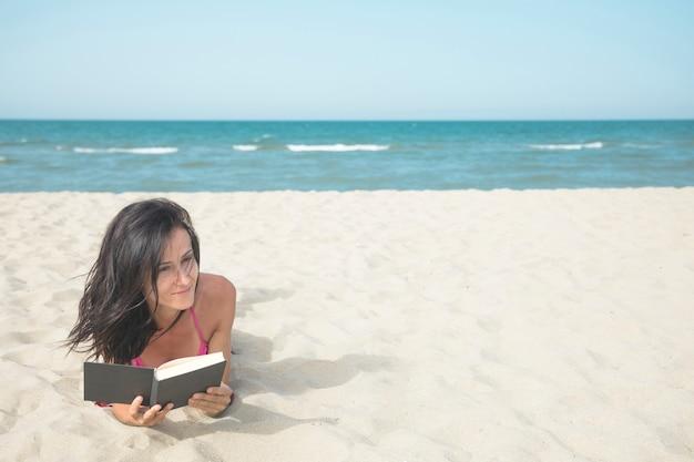 Femme, plage, lecture livre Photo gratuit