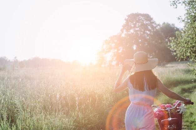 Femme en plein air avec vélo vintage et un panier de fleurs et admirant le coucher du soleil contre Photo Premium