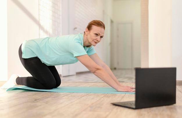 Femme Plein Coup Sur Tapis De Yoga Photo gratuit