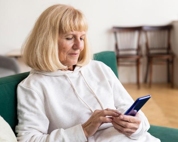 Femme Plus âgée à L'aide De Smartphone à La Maison Photo gratuit