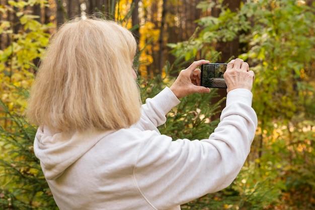 Femme Plus âgée à L'aide De Smartphone Pour Prendre Des Photos De La Nature Photo gratuit