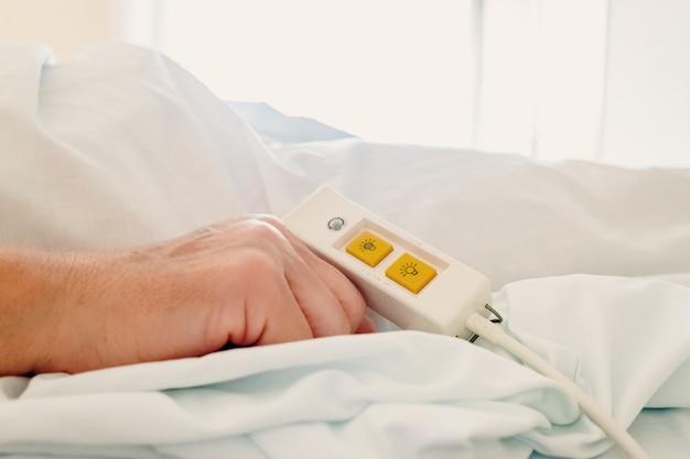Une Femme Plus âgée Allongée Dans Son Lit D'hôpital En Utilisant La Commande D'assistance. Photo Premium