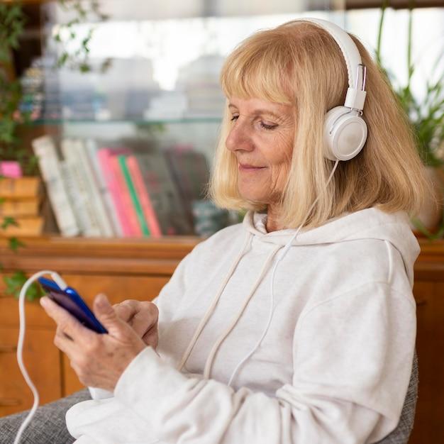 Femme Plus âgée Appréciant La Musique à La Maison Sur Les écouteurs Photo gratuit