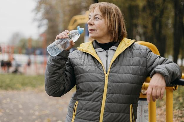 Femme Plus âgée Buvant De L'eau Après Avoir Travaillé à L'extérieur Photo gratuit