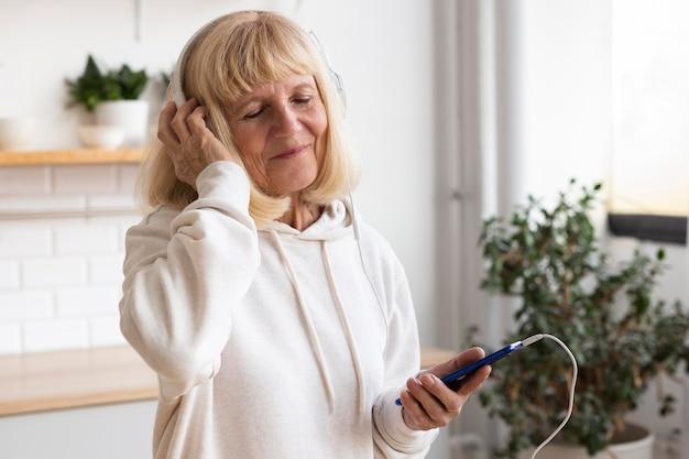 Femme Plus âgée Avec Un Casque Et Un Smartphone à La Maison Photo gratuit