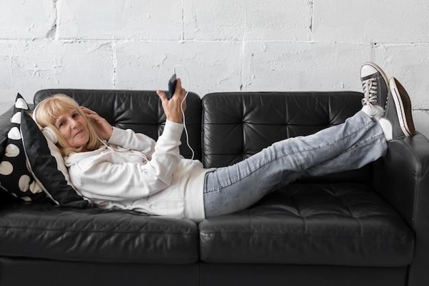 Femme Plus âgée, écouter De La Musique Sur Un Canapé à La Maison Photo gratuit