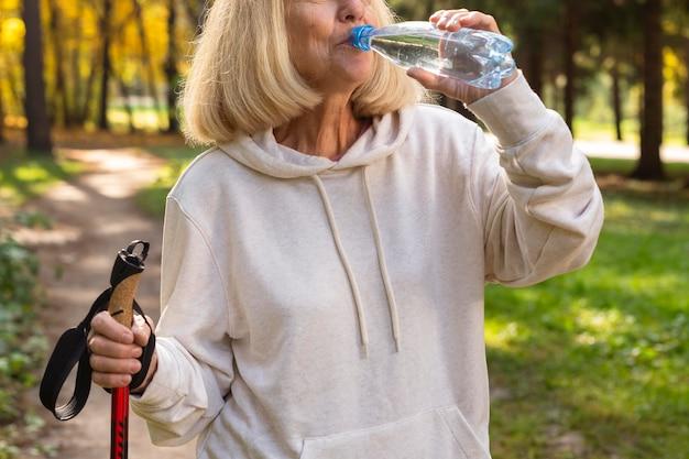 Femme Plus âgée à L'extérieur De L'eau Potable Pendant Le Trekking Photo gratuit