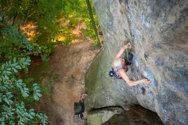 Femme plus âgée grimpeur grimpe avec des carabines et de la corde sur un mur rocheux de gros rocher. Photo Premium