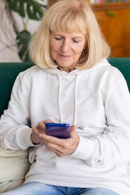 Femme Plus âgée à La Maison à L'aide De Smartphone Sur Le Canapé Photo gratuit