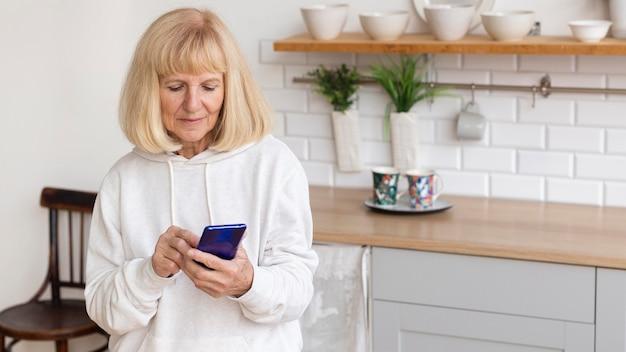 Femme Plus âgée à La Maison à L'aide De Smartphone Avec Espace De Copie Photo gratuit
