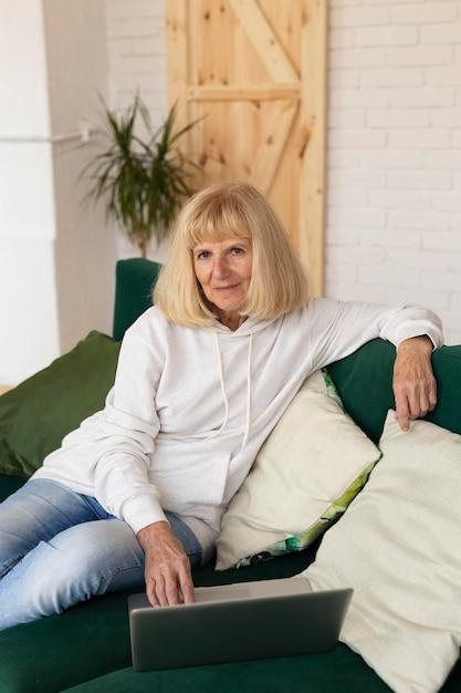 Femme Plus âgée à La Maison Sur Le Canapé Avec Ordinateur Portable Photo gratuit