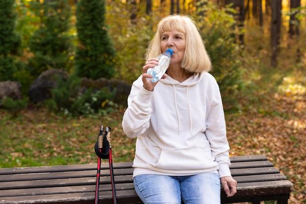 Femme Plus âgée En Plein Air Trekking Et Eau Potable Photo gratuit