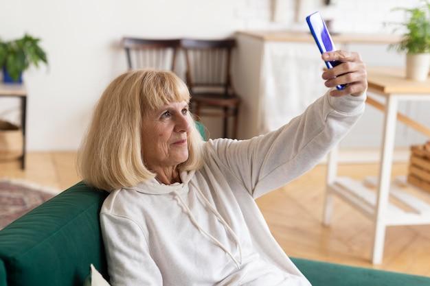 Femme Plus âgée Prenant Un Selfie à La Maison Photo gratuit