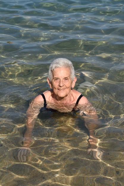 Femme plus âgée se baignant dans la mer, Photo Premium